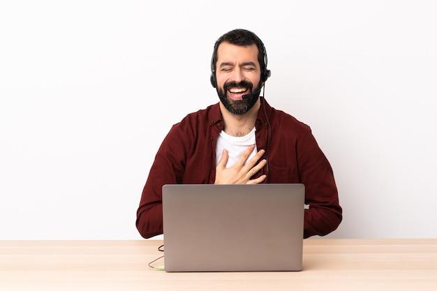 Telemarketer kaukaski mężczyzna pracujący z zestawem słuchawkowym i laptopem dużo się uśmiecha