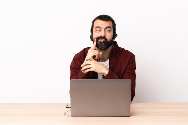 Telemarketer kaukaski mężczyzna pracujący z zestawem słuchawkowym i laptopem i myśleniem.
