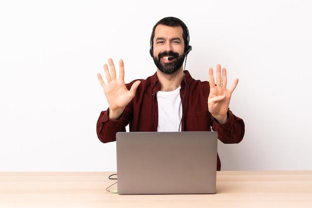 Telemarketer kaukaski mężczyzna pracujący z zestawem słuchawkowym i laptopem, licząc dziewięć palcami.