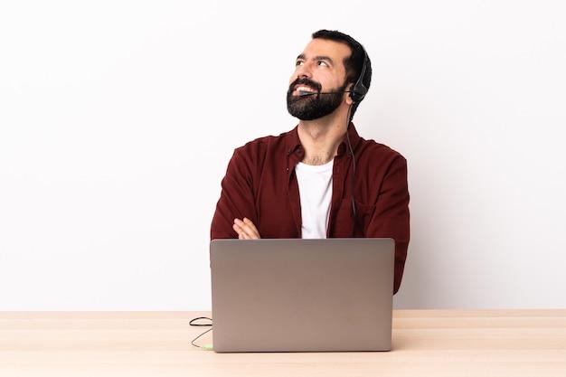 Telemarketer kaukaski mężczyzna pracujący z zestawem słuchawkowym i laptopem patrząc w górę podczas uśmiechu.