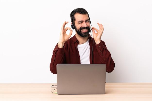 Telemarketer kaukaski mężczyzna pracujący z zestawem słuchawkowym i laptopem pokazujący znak ok palcami.