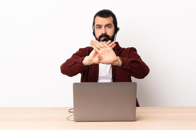 Telemarketer kaukaski mężczyzna pracujący z zestawem słuchawkowym i laptopem robi gestem ręką, aby zatrzymać akt