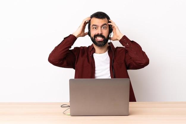 Telemarketer kaukaski mężczyzna pracujący z zestawem słuchawkowym i laptopem robi nerwowy gest