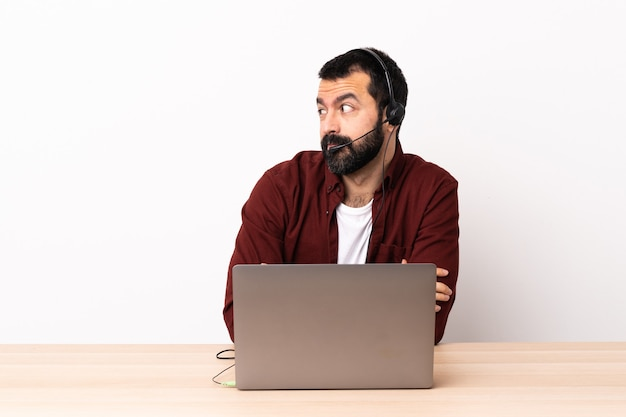 Telemarketer kaukaski mężczyzna pracujący z zestawem słuchawkowym i laptopem robiącym wątpliwość gestem patrząc z boku.