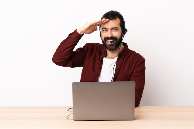 Telemarketer kaukaski mężczyzna pracujący z zestawem słuchawkowym i laptopem salutując ręką z radosnym wyrazem twarzy.