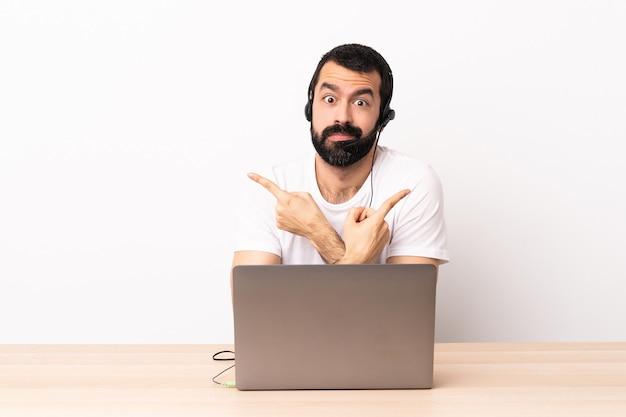 Telemarketer kaukaski mężczyzna pracujący z zestawem słuchawkowym i laptopem wskazujący na części boczne, mający wątpliwości.