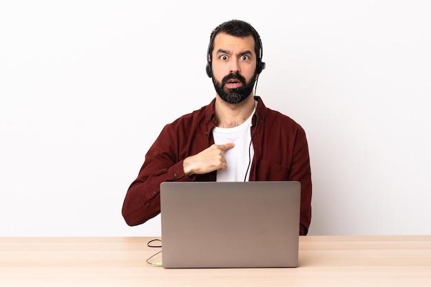 Telemarketer kaukaski mężczyzna pracujący z zestawem słuchawkowym i laptopem wskazującym na siebie.
