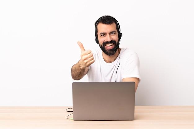 Telemarketer kaukaski mężczyzna pracujący z zestawem słuchawkowym i laptopem z podniesionymi kciukami, ponieważ wydarzyło się coś dobrego.