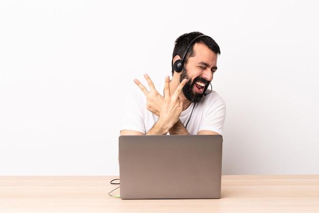 Telemarketer kaukaski mężczyzna pracujący z zestawem słuchawkowym i laptopem z uśmiechem