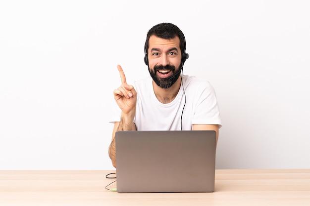 Telemarketer kaukaski mężczyzna pracujący z zestawem słuchawkowym i laptopem zamierzający wykonać rozwiązanie podnosząc palec w górę.