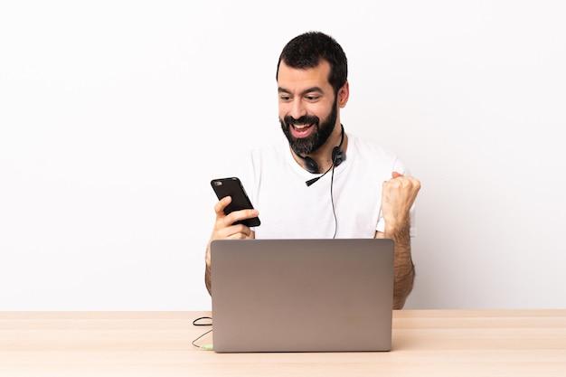 Telemarketer kaukaski mężczyzna pracujący z zestawem słuchawkowym i laptopem zaskoczony i wysyłający wiadomość.