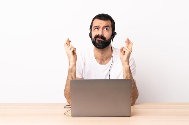 Telemarketer kaukaski mężczyzna pracujący z zestawem słuchawkowym i laptopem ze skrzyżowanymi palcami i życzący wszystkiego najlepszego.