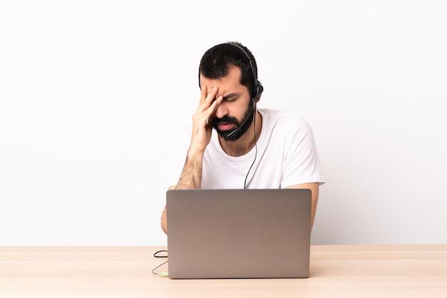 Telemarketer kaukaski mężczyzna pracujący z zestawem słuchawkowym i laptopem ze zmęczonym i chorym wyrazem twarzy.