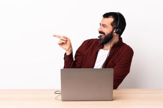 Telemarketer kaukaski mężczyzna pracujący z zestawem słuchawkowym i laptopem