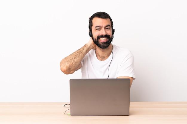 Telemarketer kaukaski mężczyzna pracujący z zestawem słuchawkowym i śmiejąc się z laptopa.