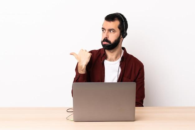 Telemarketer kaukaski mężczyzna pracujący z zestawu słuchawkowego i laptopa niezadowolony i wskazując na bok