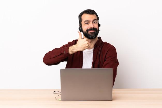 Telemarketer kaukaski mężczyzna pracujący z zestawu słuchawkowego i laptopa podając kciuki gest