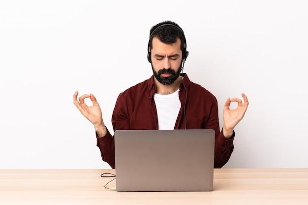Telemarketer kaukaski mężczyzna pracujący z zestawu słuchawkowego i laptopa w pozie zen