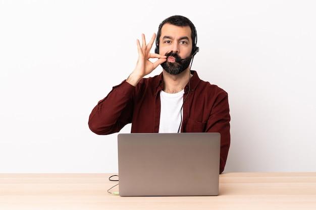 Telemarketer kaukaski mężczyzna pracujący z zestawu słuchawkowego i laptopa wykazujące znak gestu ciszy