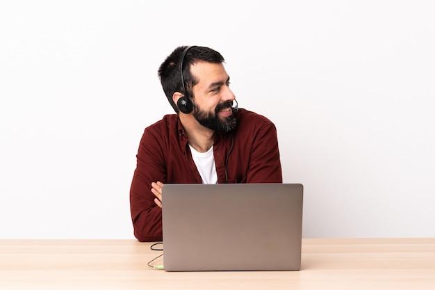 Telemarketer kaukaski mężczyzna pracujący z zestawu słuchawkowego i laptopa z rękami skrzyżowanymi i szczęśliwy