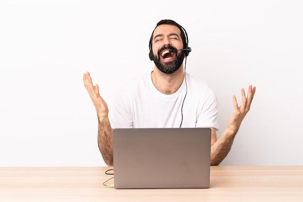 Telemarketer kaukaski mężczyzna pracuje z zestawem słuchawkowym i laptopem uśmiecha się