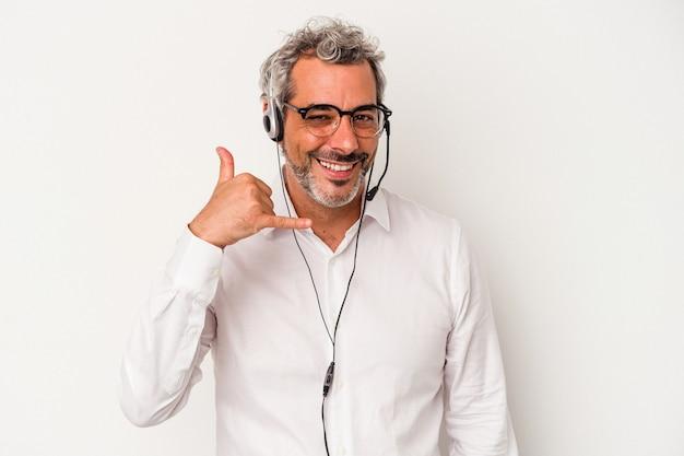 Telemarketer kaukaski mężczyzna w średnim wieku na białym tle pokazujący gest połączenia z telefonem komórkowym palcami.
