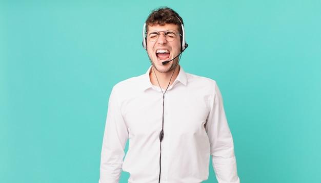 """Telemarketer krzyczy agresywnie, wygląda na bardzo rozgniewanego, sfrustrowanego, oburzonego lub zirytowanego, krzyczy """"nie"""""""