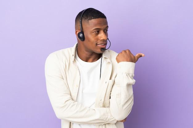 Telemarketer łaciński mężczyzna pracujący z zestawem słuchawkowym na fioletowym tle, wskazując w bok, aby zaprezentować produkt