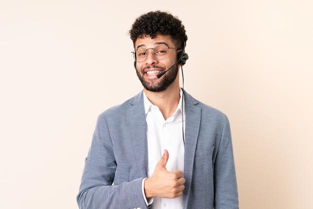 Telemarketer marokański mężczyzna pracujący z zestawem słuchawkowym na beżowej ścianie, dając kciuk w górę gestem