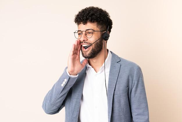 Telemarketer marokański mężczyzna pracujący z zestawem słuchawkowym na beżowej ścianie krzyczący z szeroko otwartymi ustami na bok