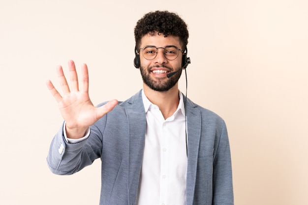 Telemarketer marokański mężczyzna pracujący z zestawem słuchawkowym na beżowej ścianie liczący pięć palcami