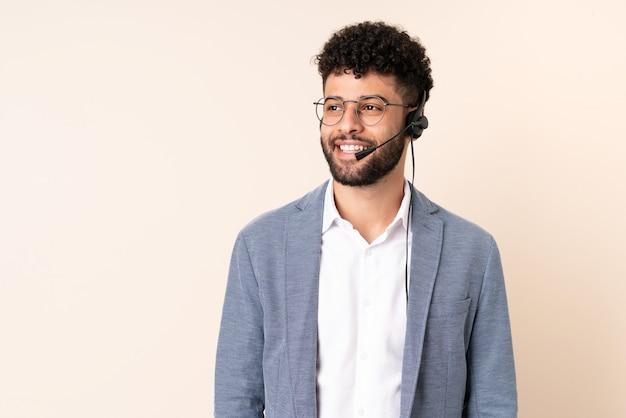 Telemarketer marokański mężczyzna pracujący z zestawem słuchawkowym na beżowej ścianie, myśląc o pomyśle, patrząc w górę