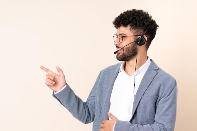 Telemarketer marokański mężczyzna pracujący z zestawem słuchawkowym na beżowej ścianie wskazując palcem w bok