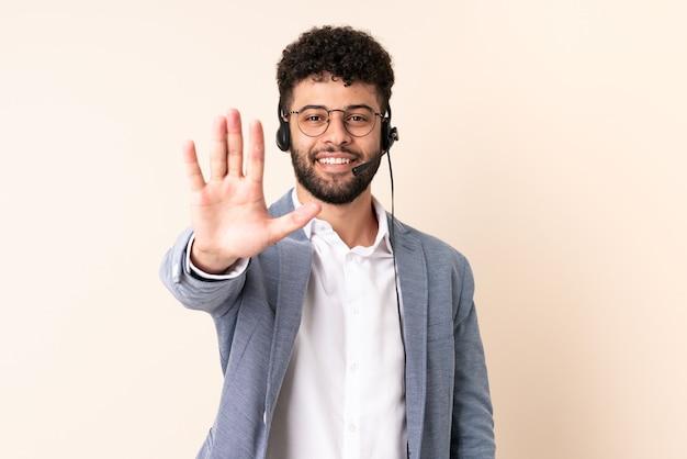 Telemarketer marokański mężczyzna pracujący z zestawem słuchawkowym na beżowej ścianie wykonujący gest stopu