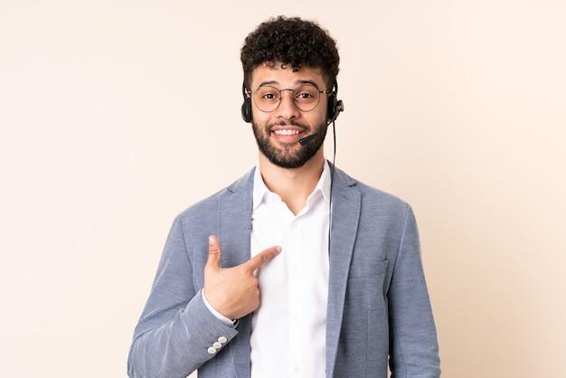 Telemarketer marokański mężczyzna pracujący z zestawem słuchawkowym na beżowej ścianie z wyrazem twarzy zaskoczenia