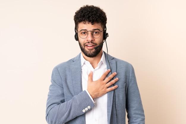 Telemarketer marokański mężczyzna pracujący z zestawem słuchawkowym na beżowej ścianie zaskoczony i zszokowany, patrząc w prawo