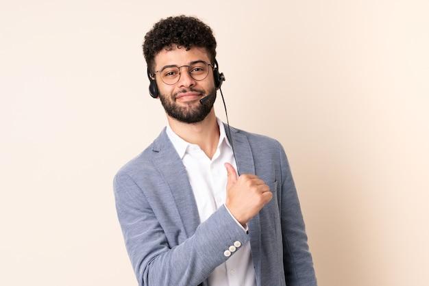Telemarketer marokański mężczyzna pracujący z zestawem słuchawkowym na beżowym tle dumny i zadowolony z siebie
