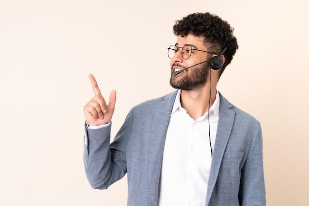 Telemarketer marokański mężczyzna pracujący z zestawem słuchawkowym na beżowym tle, wskazując na świetny pomysł