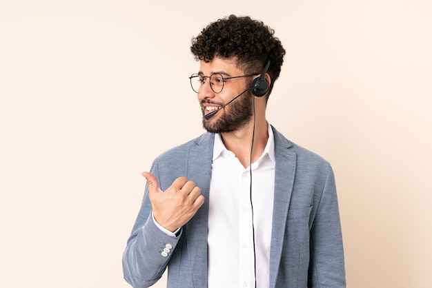 Telemarketer marokański mężczyzna pracujący z zestawem słuchawkowym na beżowym tle, wskazując w bok, aby zaprezentować produkt