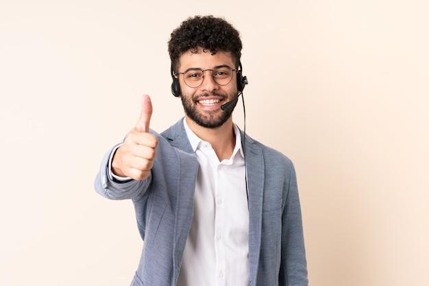 Telemarketer marokański mężczyzna pracujący z zestawem słuchawkowym na beżowym tle z kciukami do góry, ponieważ wydarzyło się coś dobrego