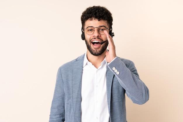 Telemarketer marokański mężczyzna pracujący z zestawem słuchawkowym na beżowym tle z zaskoczeniem i zszokowanym wyrazem twarzy