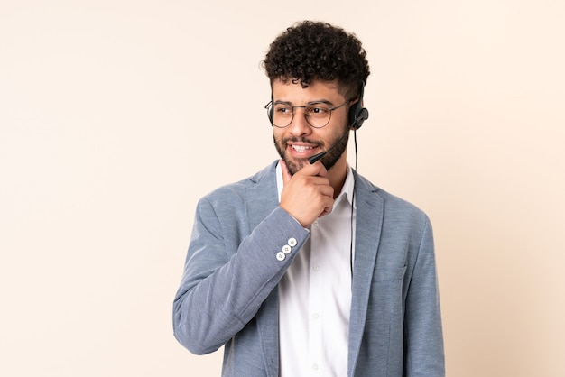 Telemarketer marokański mężczyzna pracujący z zestawem słuchawkowym na białym tle na beż patrząc z boku i uśmiechnięty