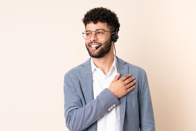 Telemarketer marokański mężczyzna pracujący z zestawem słuchawkowym na białym tle na beżowej ścianie patrząc w górę z uśmiechem