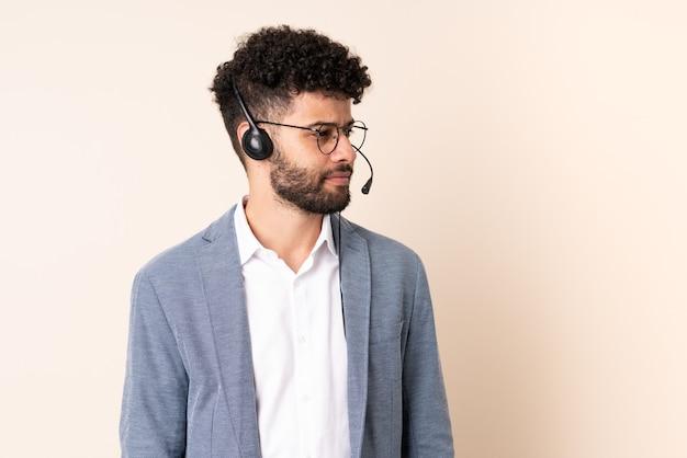Telemarketer marokański mężczyzna pracujący z zestawem słuchawkowym na białym tle na beżowej ścianie, patrząc z boku