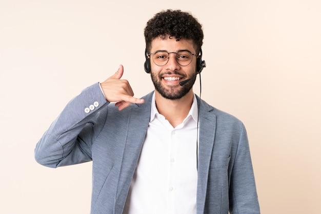 Telemarketer marokański mężczyzna pracujący z zestawem słuchawkowym na białym tle na beżowej ścianie wykonujący gest telefonu. oddzwoń do mnie znak