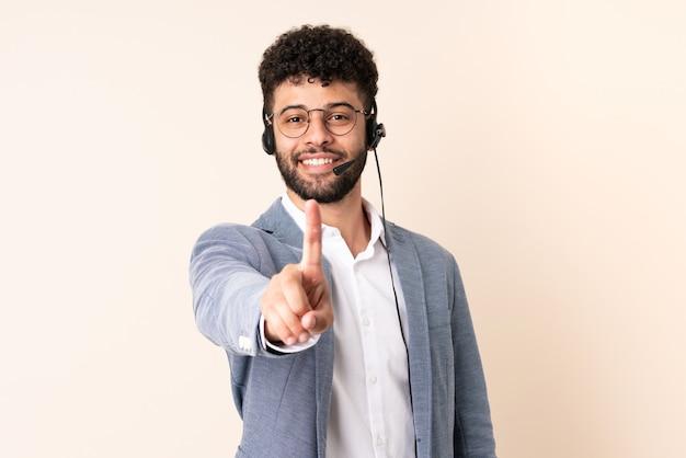 Telemarketer marokański mężczyzna pracujący z zestawem słuchawkowym na białym tle na beżowym pokazujący i podnoszący palec