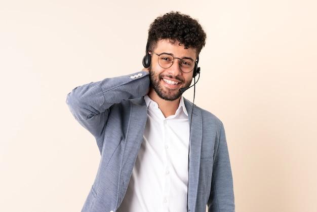 Telemarketer marokański mężczyzna pracujący z zestawem słuchawkowym na białym tle na beżowym śmiechu