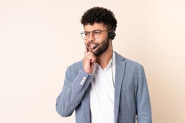 Telemarketer marokański mężczyzna pracujący z zestawem słuchawkowym na białym tle na beżowym tle myśli pomysł, patrząc w górę