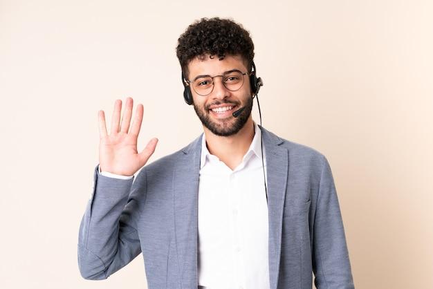 Telemarketer marokański mężczyzna pracujący z zestawem słuchawkowym na białym tle na beżowym tle, salutując ręką z radosnym wyrazem twarzy