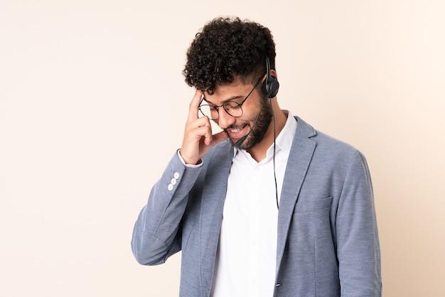 Telemarketer marokański mężczyzna pracujący z zestawem słuchawkowym na białym tle na beżowym tle, śmiejąc się